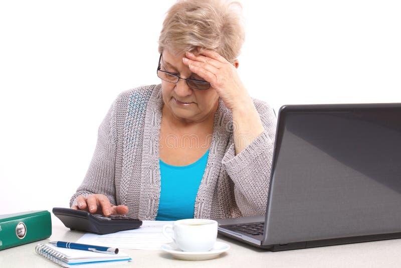 Потревоженная пожилая старшая женщина подсчитывая счета за коммунальные услуги на ее доме, финансовом материальном обеспечении в  стоковое фото