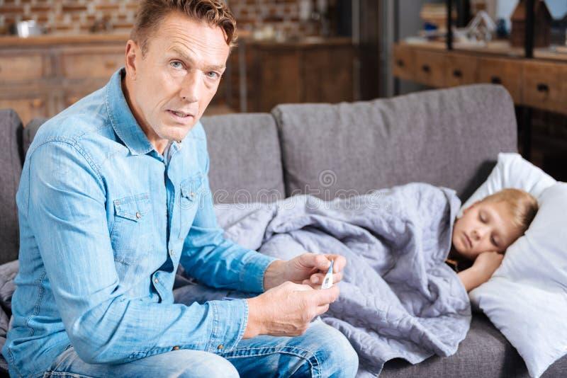 Потревоженная температура отца измеряя его больного сына стоковая фотография