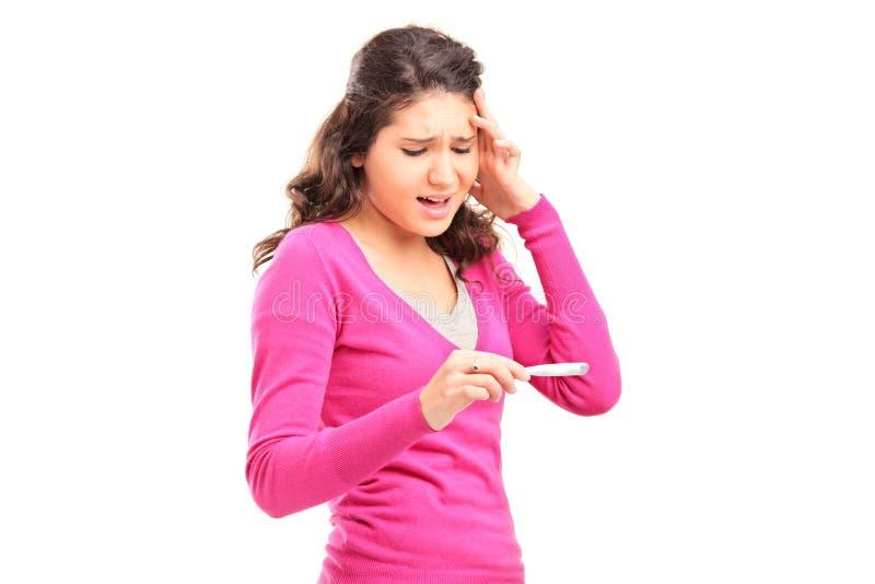 Потревоженное молодое женское проверяя испытание стельности стоковое фото