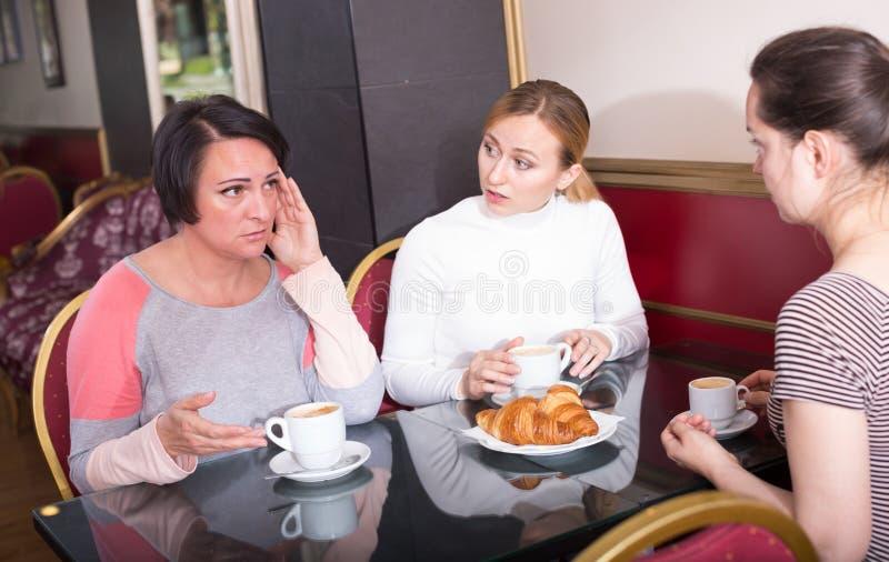 Потревоженные женщины выпивая кофе в столовой стоковое изображение