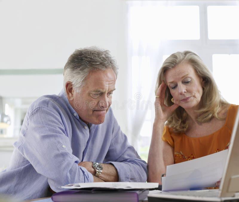 Потревоженные зрелые пары с счетами на обеденном столе стоковые фотографии rf