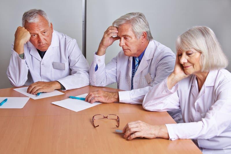 Потревоженные доктора думая в встрече стоковое изображение