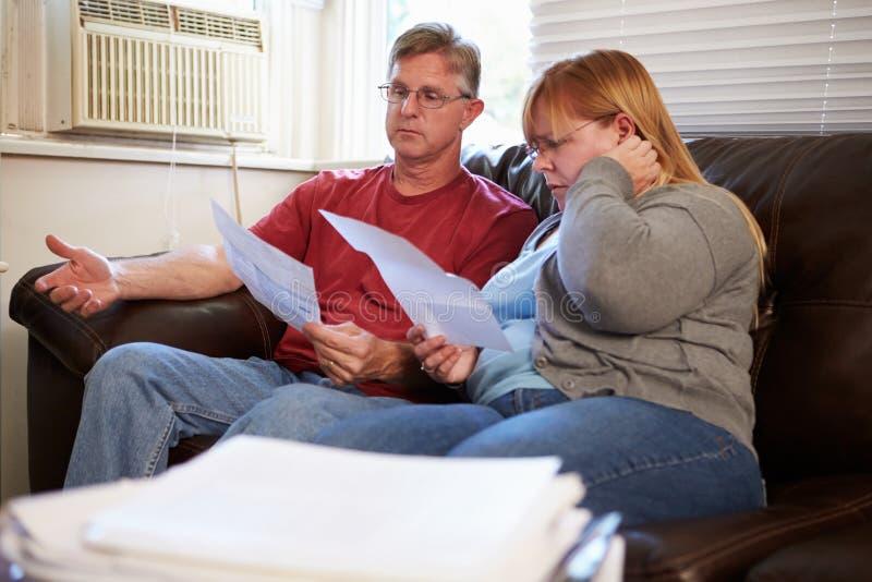 Потревоженные пары сидя на софе смотря счеты стоковые фотографии rf