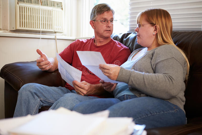 Потревоженные пары сидя на софе смотря счеты стоковое изображение rf