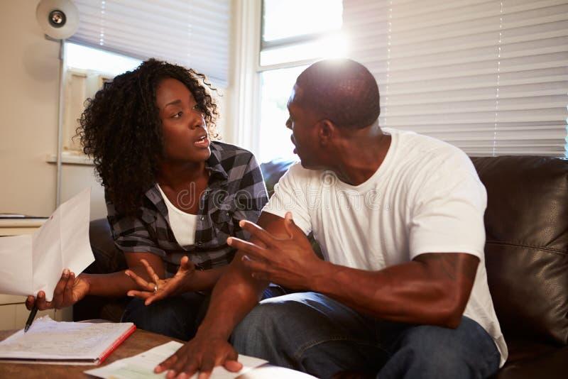 Потревоженные пары сидя на софе споря о счетах стоковые фотографии rf