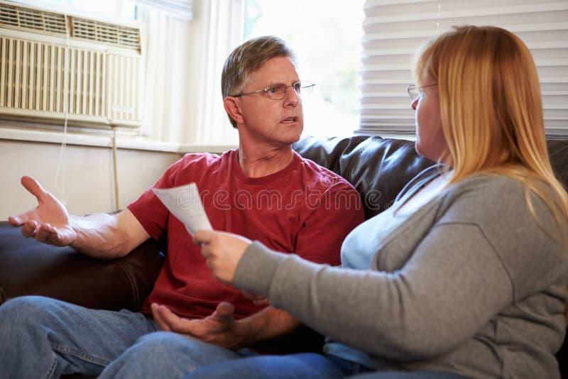Потревоженные пары сидя на софе споря о счетах стоковое изображение