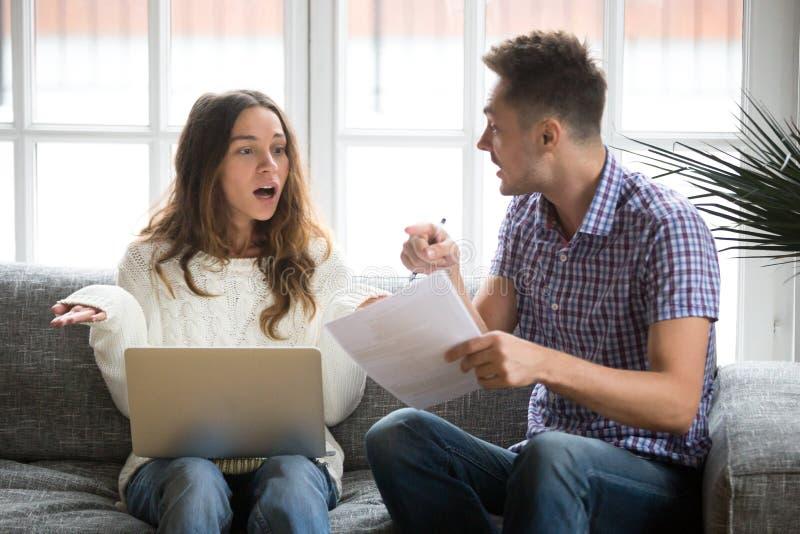 Потревоженные пары споря о счетах задолженности с компьтер-книжкой и документом стоковые изображения rf