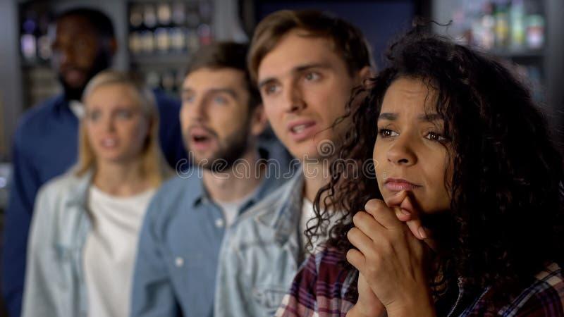 Потревоженные сторонники команды смотря конкуренцию ТВ, группу в составе вентиляторы на спортивном мероприятии стоковое фото