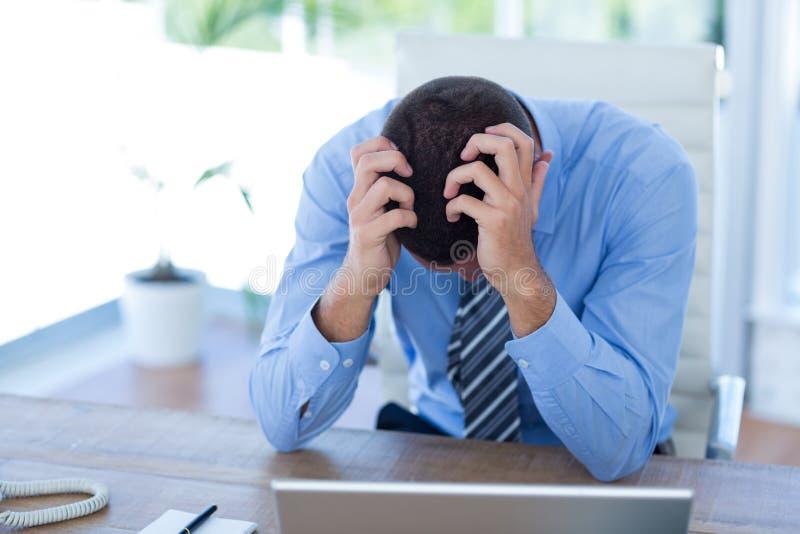 Потревоженный бизнесмен с головой в руках стоковые фотографии rf