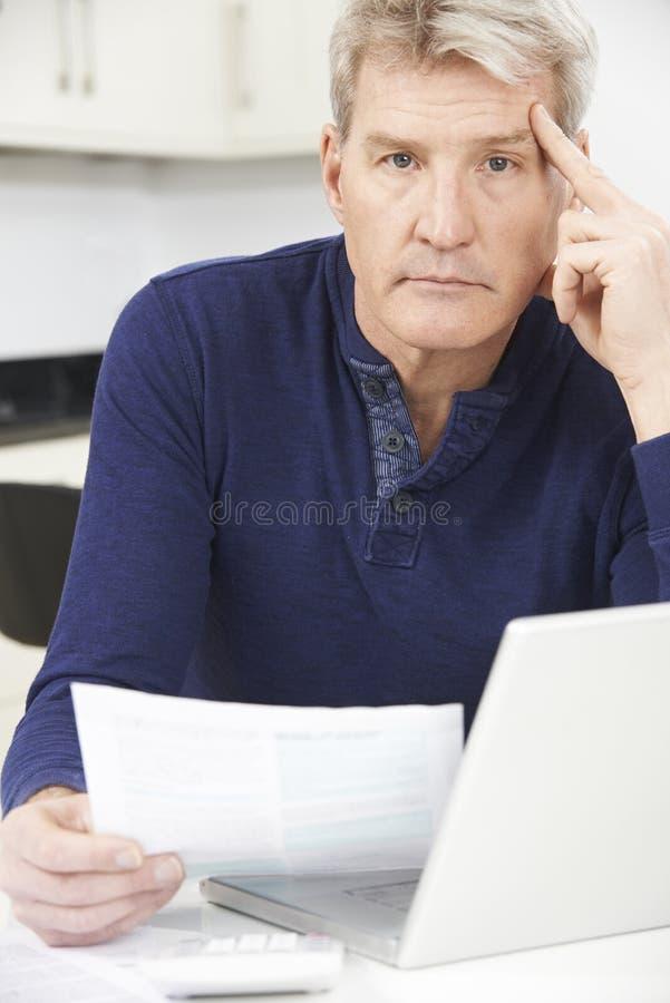 Потревоженный зрелый человек смотря рассматривающ финансы дома стоковые фото