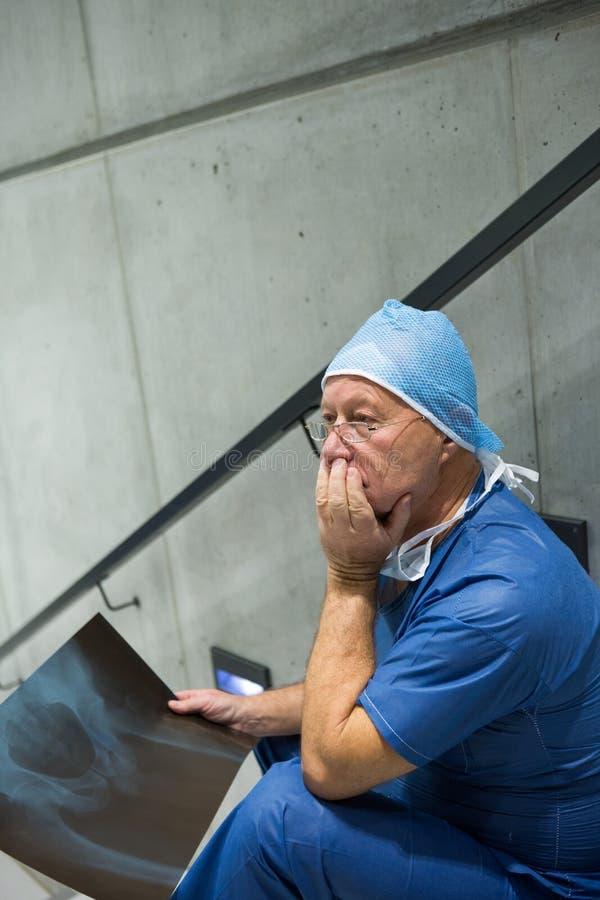 Потревоженный мужской хирург держа рентгеновский снимок на лестнице стоковая фотография