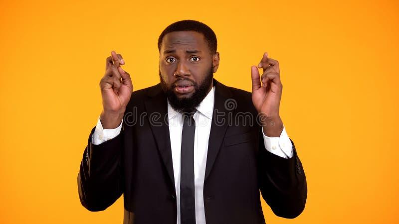 Потревоженный смешной суеверный афро-американский человек в интервью пальцев костюма пересекая стоковое фото rf