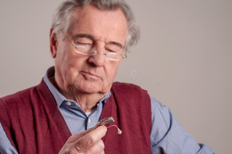Потревоженный старший человек держа слуховой аппарат стоковое изображение