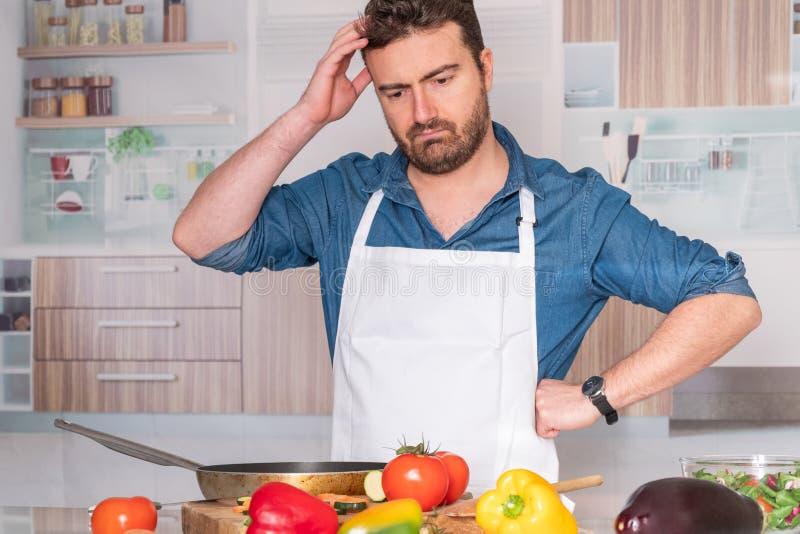 Потревоженный человек перед варить дома для обедающего стоковое изображение