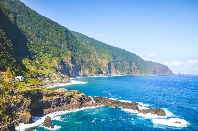 Потрясающие скалы на северном побережье острова Мадейра, Португалия Суровые зеленые камни, небольшой город и темно-синяя вода стоковое фото rf
