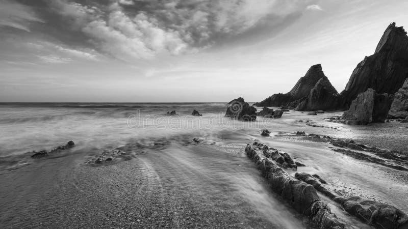 Потрясающий черно-белый пейзаж заката: изображение пляжа Уэсткомбе в Девон Англия стоковое фото