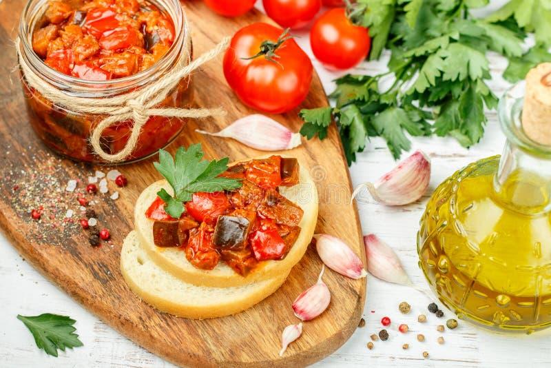 Потушенные овощи баклажан, болгарские перцы и томаты с чесноком, петрушкой и специями на тосте хлеба стоковые изображения