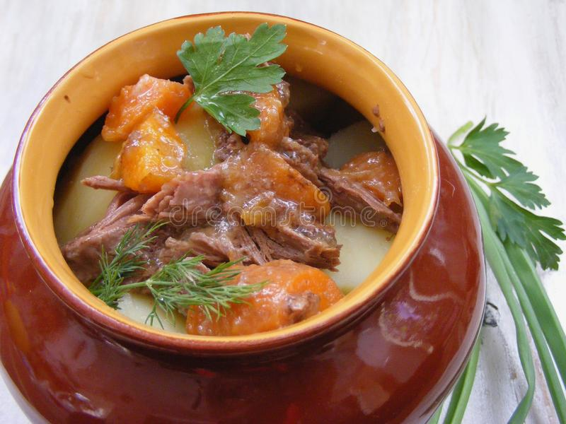 Потушенный кролик с овощами, гуляш оленины в медном баке на деревянной поверхности, зажарил в духовке мясо говядины с морковью, л стоковая фотография