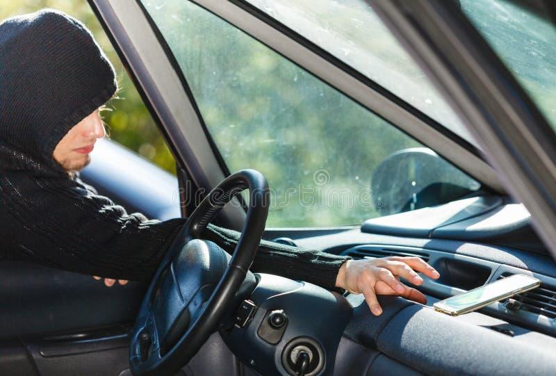 Похититель взломщика ломая в smartphone красть автомобиля стоковое фото rf