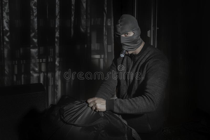 Похититель в маске и с электрофонарем в комнате кладет добычу в сумку стоковая фотография