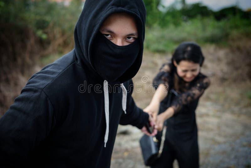 Похититель крадет smartphone от жертвы на луге стоковое фото