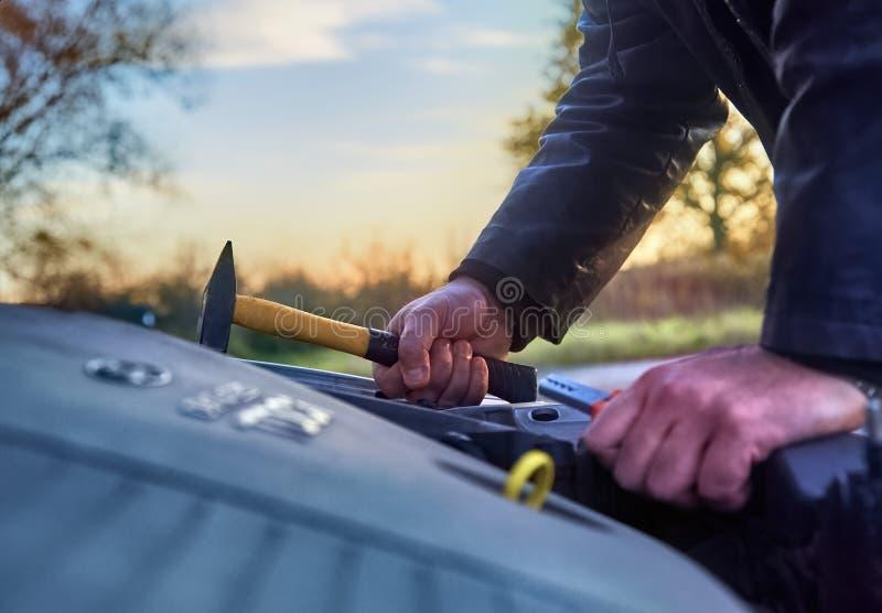 Похититель нося черные одежды крадя автомобиль стоковое фото rf