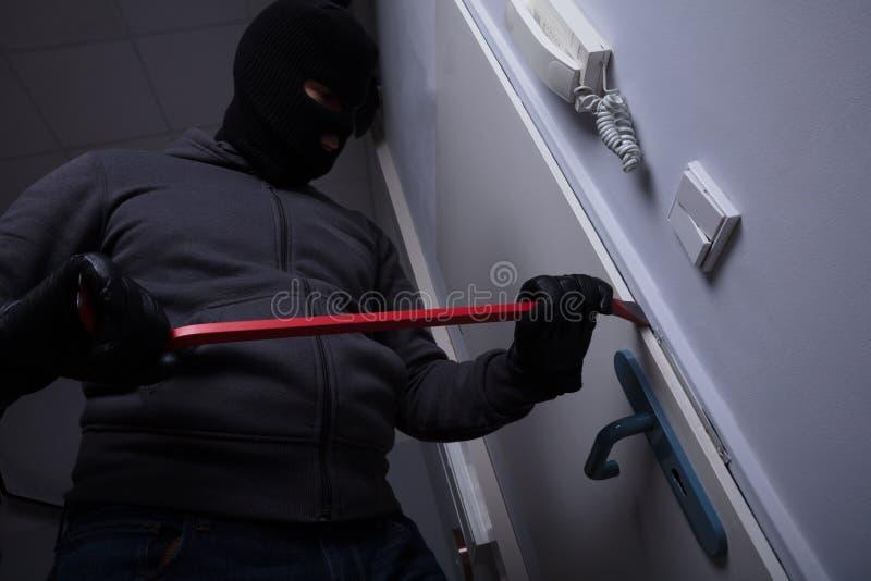 Похититель пробуя сломать дверь стоковое изображение rf