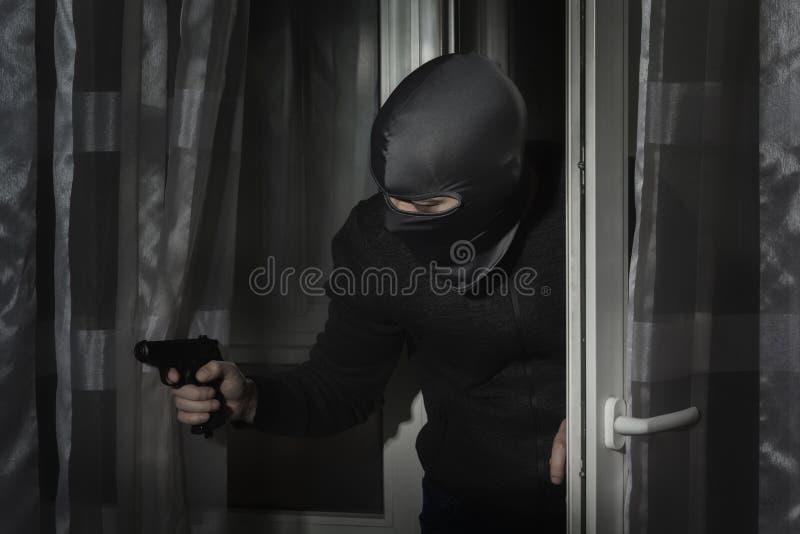 Похититель с оружием в его руке и в шляпе с разрезом для глаз крадется в дом через дверь вечером стоковое изображение