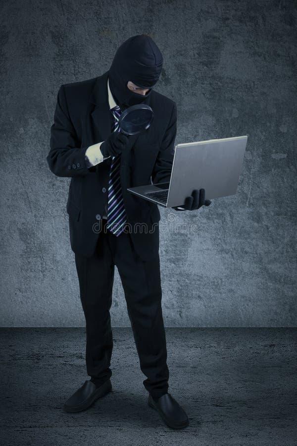 Похититель держит компьтер-книжку с увеличителем стоковое фото rf