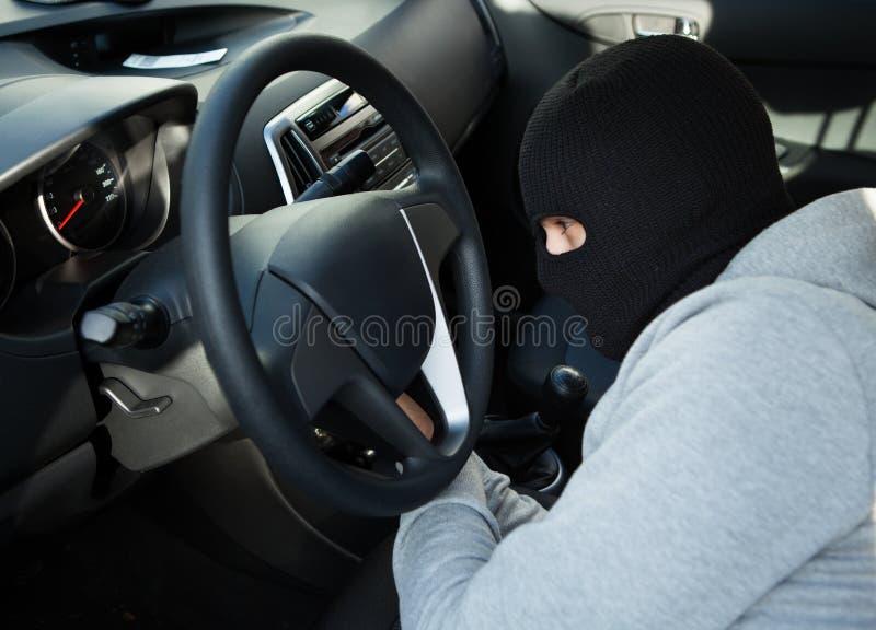 Похититель используя отвертку в автомобиле стоковое фото