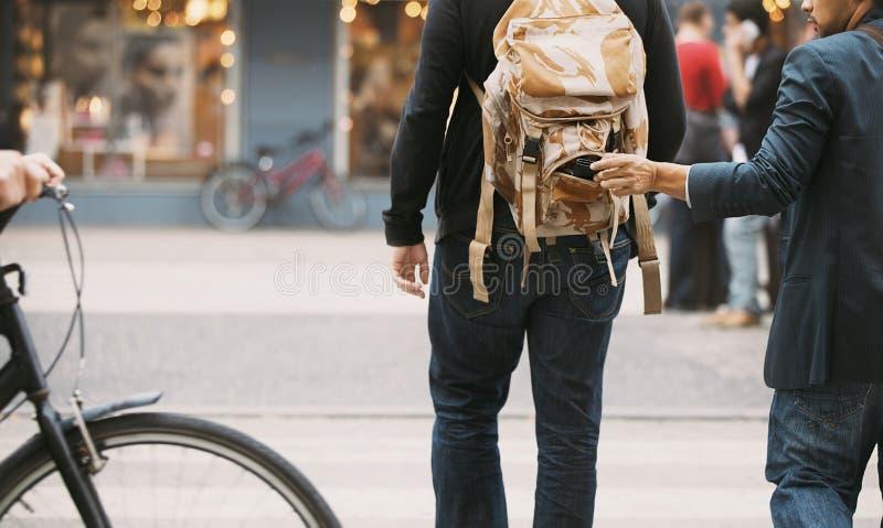Похититель крадя бумажник от рюкзака стоковое фото rf