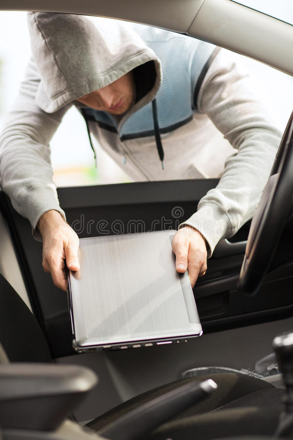 Похититель крадя компьтер-книжку от автомобиля стоковое фото