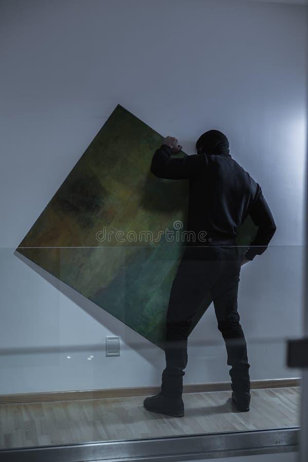 Похититель крадя дорогую картину стоковое изображение rf