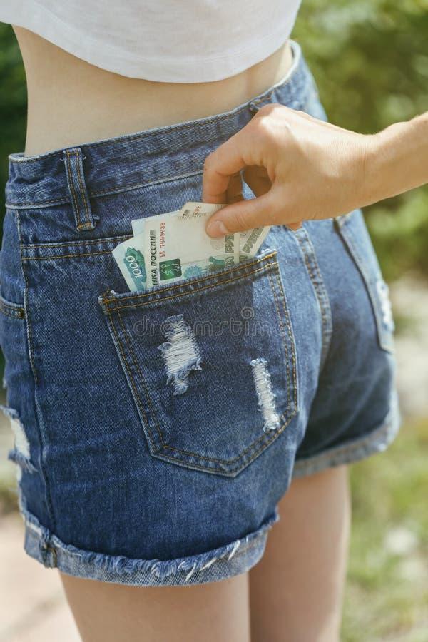 Похищение денег от заднего карманн стоковое фото rf