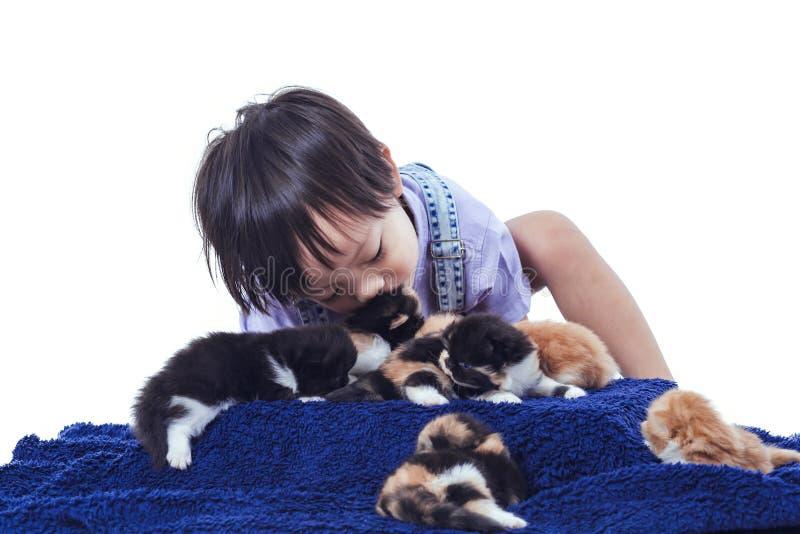 Поцелуй детей и играть котенок совместно стоковое фото