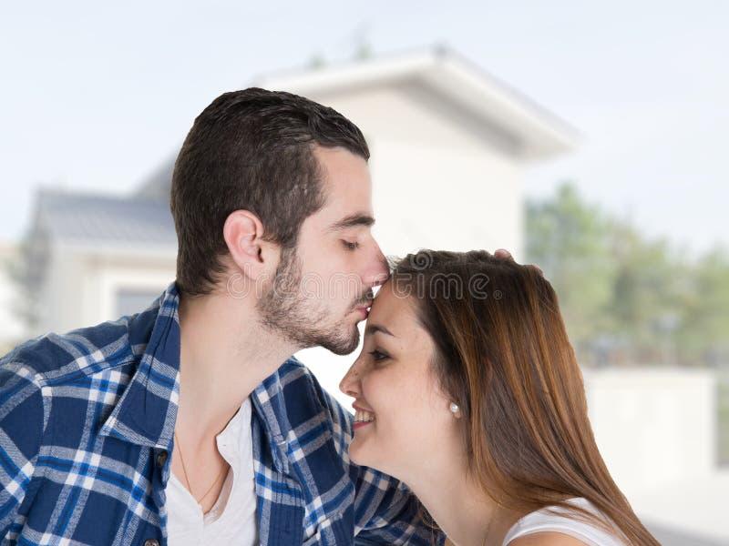 Поцелуй любит молодых пар смотря их новый современный уютный дом стоковые изображения rf
