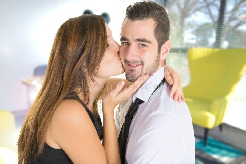 Поцелуй человека женщиной в интерьере пар очень ультрамодного и модного дома стоковое изображение