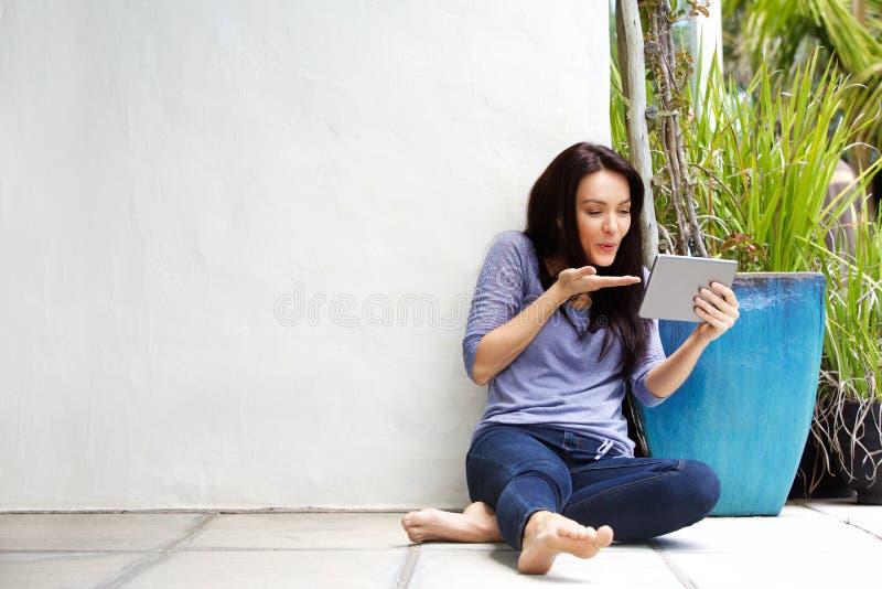 Поцелуй счастливой молодой женщины дуя на цифровой таблетке во время видео- звонка стоковая фотография rf