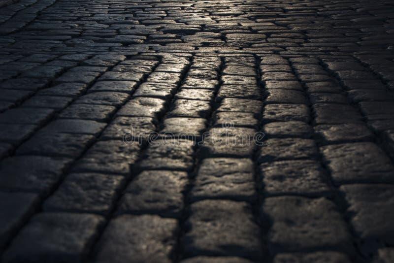 Почерните мощенную булыжником каменную предпосылку дороги при отражение света увиденное на дороге Черная или темная серая каменна стоковое фото rf