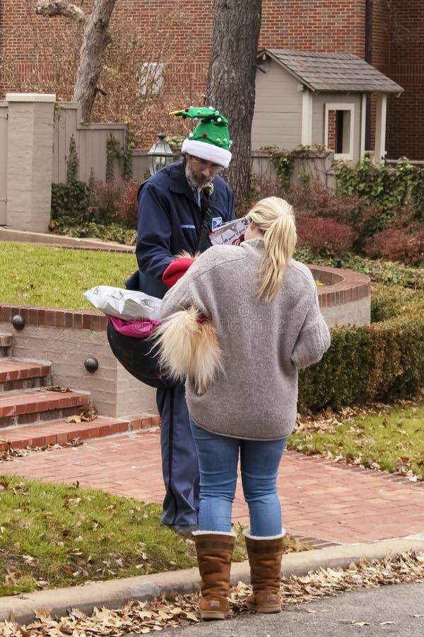 Почтальон нося зеленую шляпу эльфа рождества делая паузу в его кругах к собаке, который держит милая белокурая женщина района в с стоковое фото