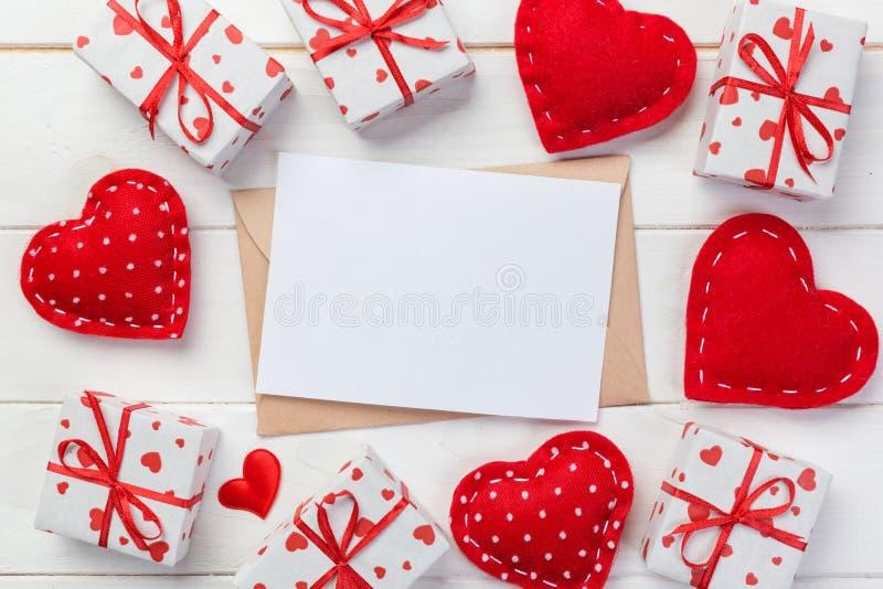 Почта конверта с красным сердцем и подарочная коробка над белой деревянной предпосылкой Карточка дня валентинки, влюбленность или стоковое изображение