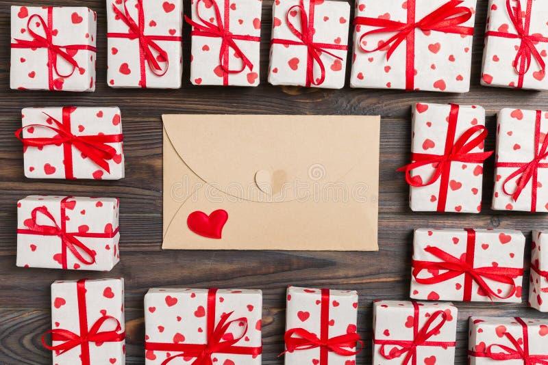 Почта конверта с красным сердцем и подарочная коробка над деревянной предпосылкой Карта дня Валентайн, любовь или дизайн концепци стоковые фотографии rf