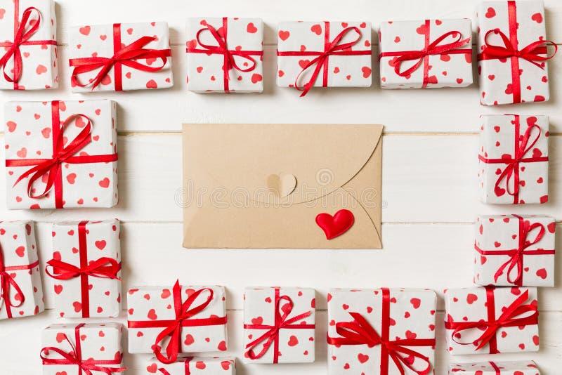 Почта конверта с красным сердцем и подарочная коробка над деревянной предпосылкой Карта дня Валентайн, любовь или дизайн концепци стоковое изображение