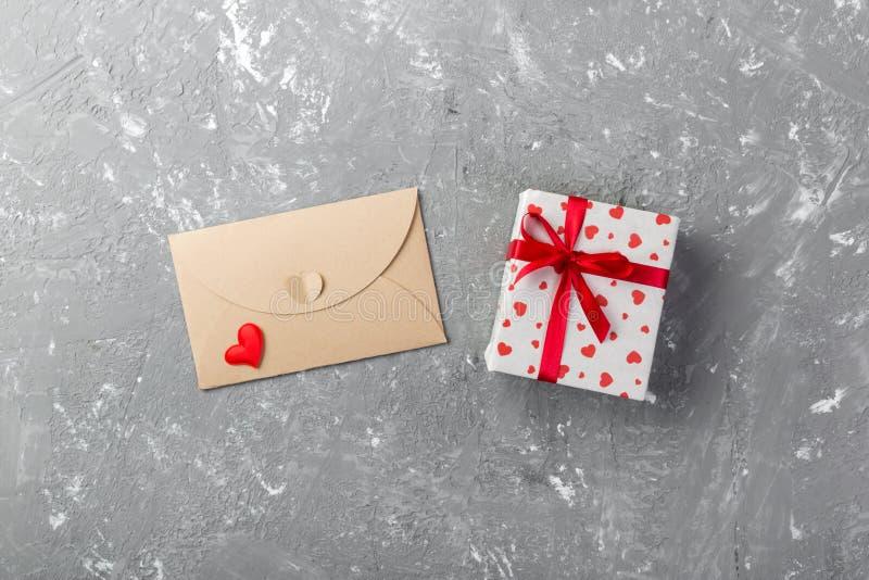 Почта конверта с красным сердцем и подарочная коробка над серой предпосылкой цемента Карточка дня валентинки, влюбленность или ко стоковые фото