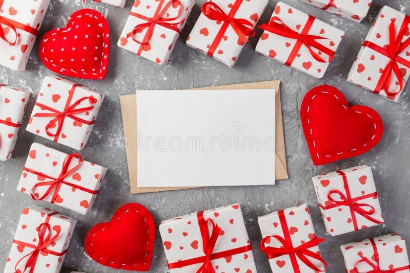 Почта конверта с красным сердцем и подарочная коробка над серой предпосылкой цемента Карточка дня валентинки, влюбленность или ко стоковое изображение
