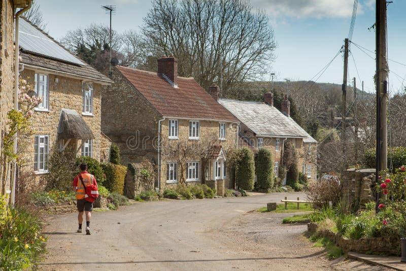Почтальон поставляет письма в английской деревне стоковая фотография rf