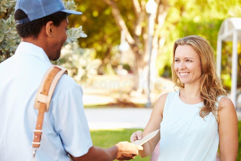 Почтальон поставляя письма к женщине стоковое фото rf