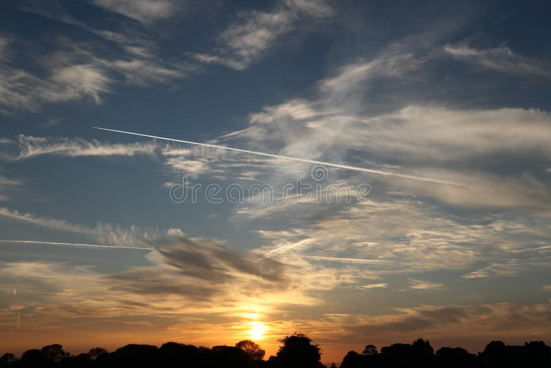 Почти установленное Солнце в облачных небесах с плоскими следами стоковая фотография