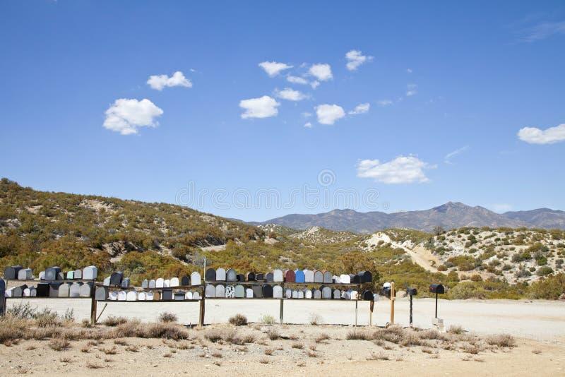 Почтовые ящики на дороге пустыни с предпосылкой горы стоковое изображение rf