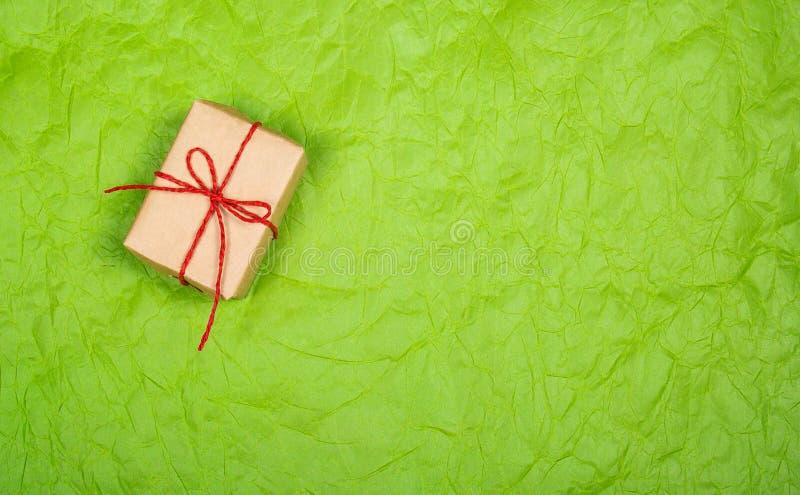 Почтовый пакет Коробка с подарком на зеленом цвете скомкала предпосылку скопируйте космос стоковое фото rf
